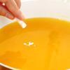 Cho vào nồi 400ml nước, 160gr đường trắng, 8gr bột rau câu dẻo, 600ml nước cam. Dùng muỗng khuấy đều để bột rau câu hòa quyện vào hỗn hợp. Đun ở lửa vừa và khuấy liên tục để rau câu không bị cháy dính dưới nồi. Khi hỗn hợp sôi thì vớt bọt, tắt bếp. Cho vào 1 ống bột vani và khuấy đều tay.