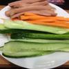 Cho cơm ra tô, thêm giấm, đường trắng, muối, trộn đều cho tất cả gia vị ngấm vào cơm để khi ăn cơm cuộn Hàn Quốc không bị nhạt nhẽo. Để cơm qua một bên. Cắt thanh nhỏ cà rốt, trụng qua nước sôi khoảng 1 phút, dưa leo cắt làm đôi, bỏ ruột, cắt thành thanh tương tự như cà rốt. Làm tương tự với xúc xích heo.