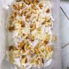 Rải 1 lớp chuối dưới hộp rồi rải dừa sợi xong rải đậu phộng, xong mình múc nước kem rưới lên, cứ làm như thế đến khi hết nguyên liệu.