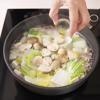 Tiếp theo, cho đậu hũ non, nấm rơm, cải thảo, miến vào, nấu đến khi sợi miến mềm là được. Nêm 1 muỗng canh nước mắm vào cho vừa ăn.