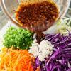 Salad ăn kèm: Trộn tất cả nguyên liệu còn lại ..xì dầu, tỏi băm, dầu mè, dấm và đường, trộn đều lại với nhau. Cho vào tô đã để sẵn, rồi trộn đều cùng bắp cải, hành lá, cà rốt đã cắt, cho đến khi rau ngấm gia vị.