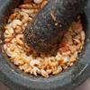 Đầu tiên, cho ớt, tỏi bóc vỏ, hành tím bóc vỏ, đường trắng vào máy xay sinh tố, xay nhuyễn. Giã nhuyễn tôm khô trong cối, cho ra chén.