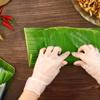 Trải lá chuối lên mặt phẳng, thêm 1 lá ổi. Cho hỗn hợp tré vào giữa. Dùng tay cuộn chặt và cột dây lạt 2 đầu cây tré. Để tré nơi thoáng mát từ 2-3 ngày để tré lên men.